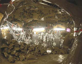 Thomas Hirschhorn: Cavemanman, 2002 • Installation: wood, cardboard, tape, aluminum foil, books, posters, videos of Lascaux 2, dolls, cans, shelves, and fluorescent light fixtures, dimensions variable. • Courtesy Barbara Gladstone  • Photo courtesy of  • The Museum of Modern Art
