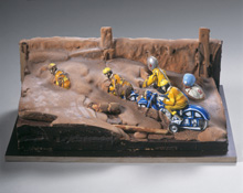 "Dieter Roth: Motorradrennfahrer III (Motorcycle racers III). 1970/1994 (reconstruction) Toy, chocolate, and painting and cooking utensils on wood, 13 x 18 1/8 x 7 1/8"" (33 x 46 x 18 cm) Dieter Roth Foundation, Hamburg Photo: Heini Schneebli, Hamburg  • Photo courtesy of The Museum of Modern Art"