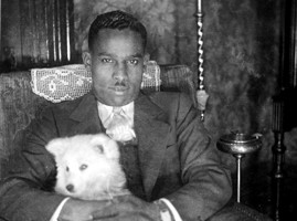 "Charles ""Teenie"" HarrisPossible self-portrait of Charles ""Teenie"" Harris seated in armchair with dog, in his home at 7604 Mulford Street, Pittsburgh, c. 1926Courtesy the Carnegie Museum of ArtPhoto courtesy of Blaffer Gallery"